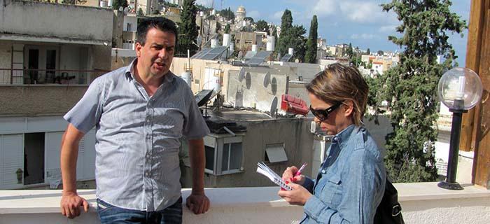 נגה כרמי ושמעון סבג על מרפסת דירה ברחוב קסל. ברקע - עמק הזיתים